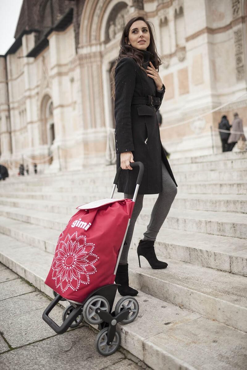 Kobieta wchodząca po schodach z wózkiem na zakupy Gimi Tris