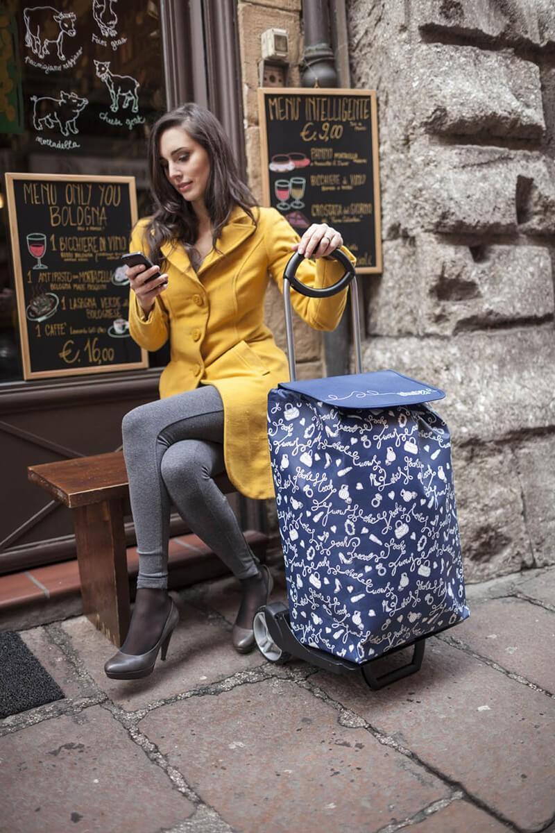 Piękna pani siedząca z wózkiem na zakupy Gimi Easy Granatowy
